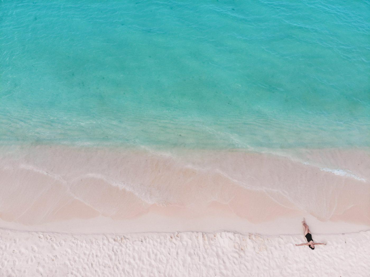 A person walking along the pristine sand and turquoise blue water of bahia de las aguilas, one of the best places to visit in the Dominican Republic.