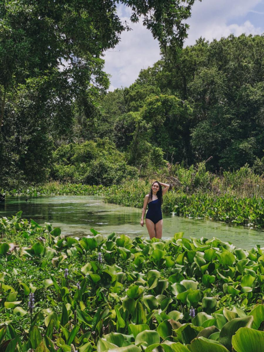 standing on a river enveloped by flowers and lush nature